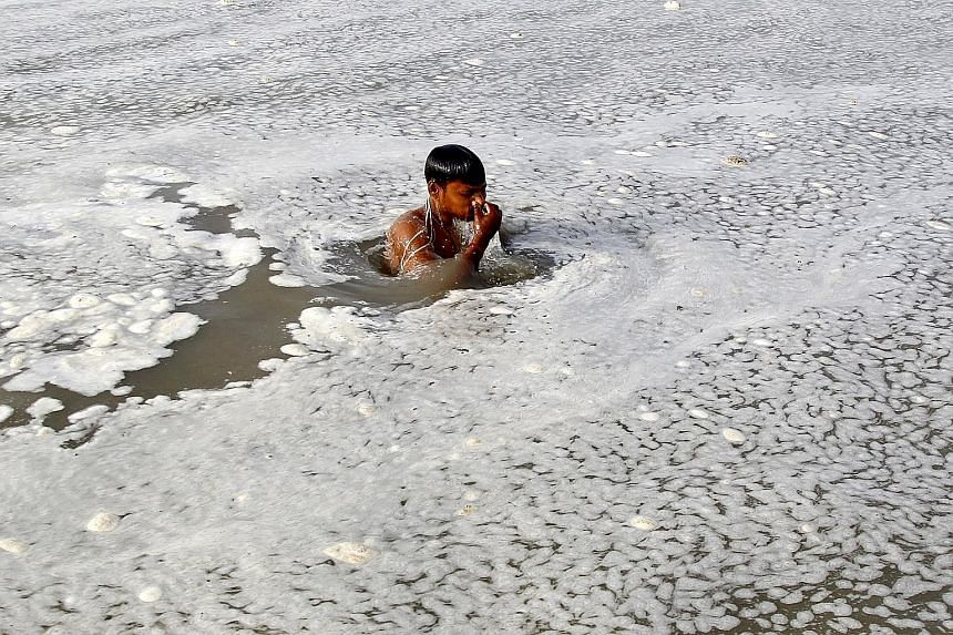 A Hindu devotee taking a dip in the polluted waters of the Ganges River in Allahabad, India.