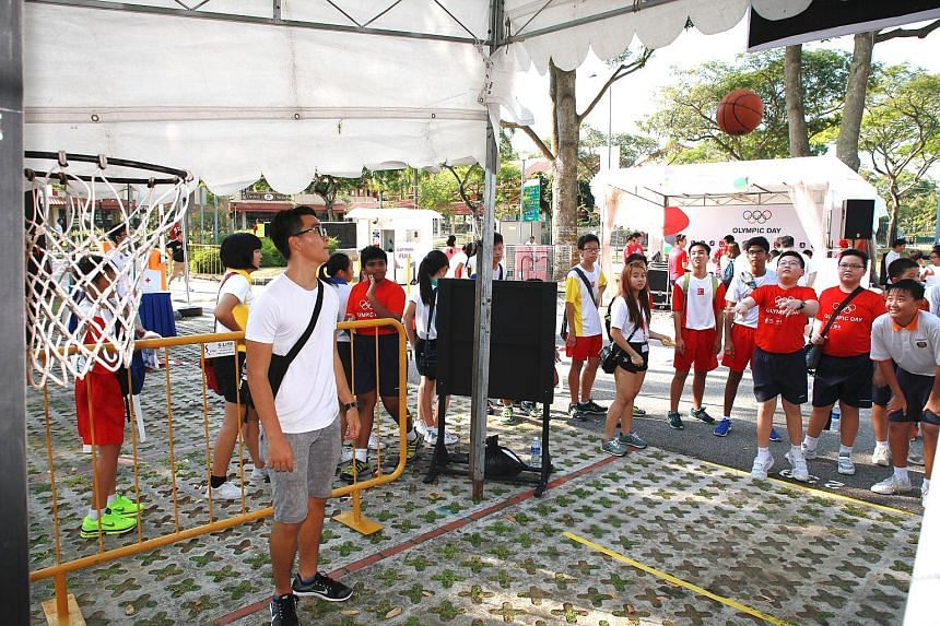 The Singapore National Olympic Council commemorated Olympic Day with a 1.9km walk from Jurong East Sports Centre yesterday. Participants (left) wore red Olympic Day T-shirts for the event, which was graced by SNOC president Tan Chuan-Jin. Before flag