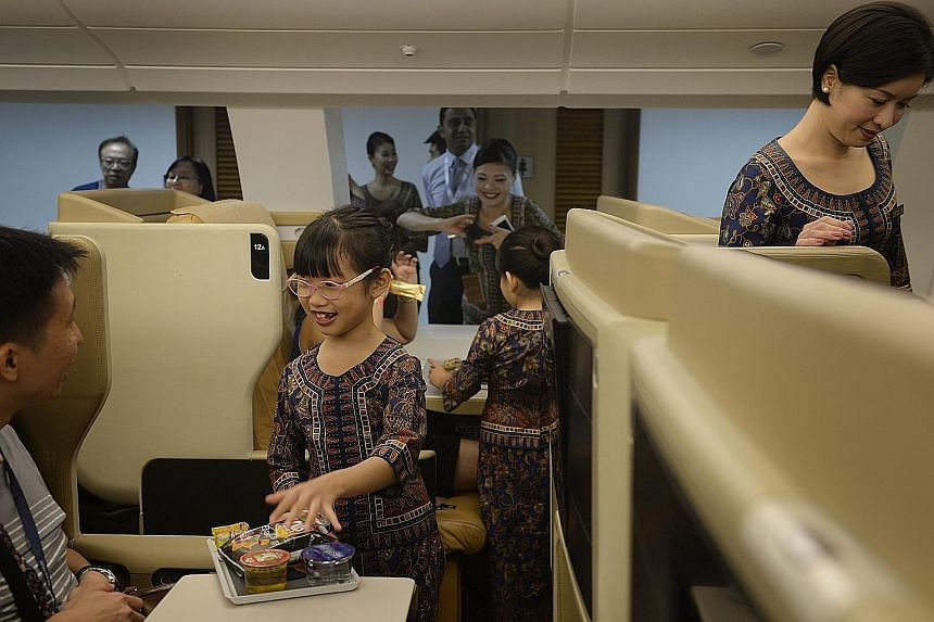 """""""Singapore Girl"""" Tan Xinyu, seven, serving her dad Tan Chee Khoon, 38, an in-flight meal in a replica of Singapore Airlines' Airbus A-380 Business Class cabin yesterday at the first SIA Training Centre Open House yesterday. The event drew more than 5"""