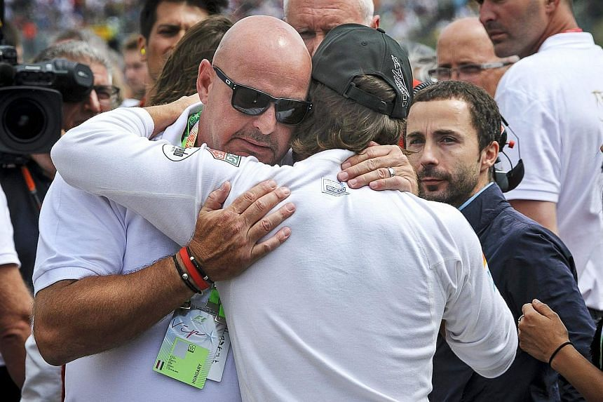 Spanish Formula One driver Fernando Alonso (centre) of McLaren Honda embraces Philippe Bianchi (left), father of French driver Jules Bianchi, during a minute of silence to pay tribute to the younger Bianchi before the Hungarian Formula One Grand Prix