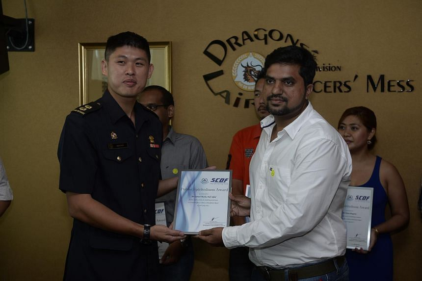 Jamal Basha Asif Iqbal receiving his award from commander of the 1st SCDF Div Alan Chow on July 26, 2015.