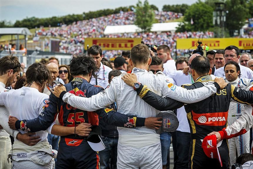 Formula One drivers embrace each other for a minute of silence to pay tribute to their recently deceased French colleague Jules Bianchi before the Hungarian Formula One Grand Prix on the Hungaroring circuit in Mogyorod, Hungary on July 26, 2015.
