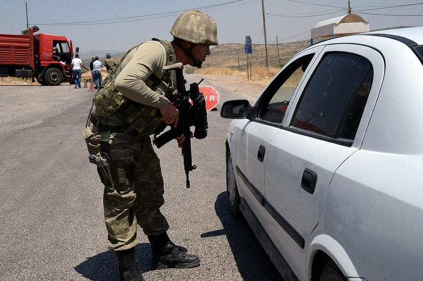A Turkish soldier checks cars at a checkpoint in Diyarbakir on July 26, 2015 following the death of two Turkish soldiers.