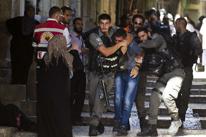 Israeli border police officers detain a Palestinian protester in Jerusalem's Old City.