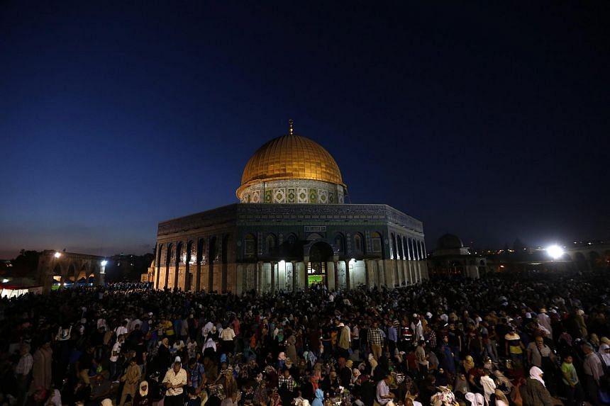 Muslim worshippers pray outside the Dome of the Rock at the al-Aqsa mosque compound in Jerusalem on July 13, 2015.