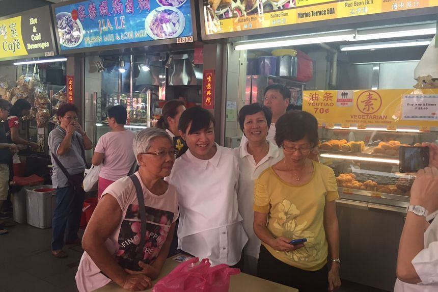 Tin Pei Ling posing for photos with MacPherson residents at Circuit Road Market and Food Centre.