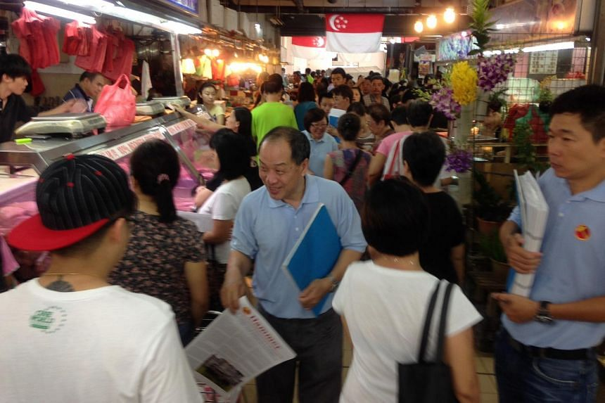 Workers' Party chief Low Thia Kiang handing out copies of the party's newsletter, The Hammer, at Rivervale Plaza.