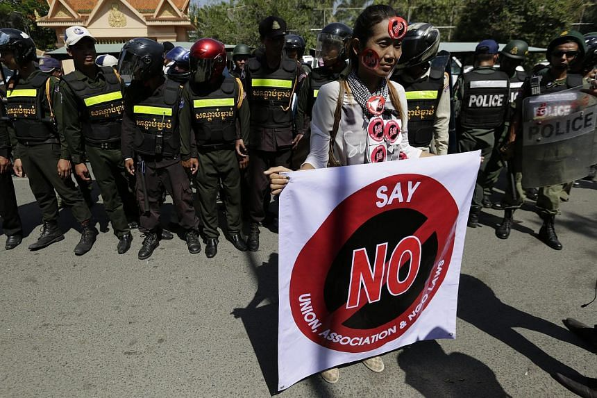 A Cambodian protester carries a banner next to police officers during a rally near the Senate in Phnom Penh, Cambodia on July 24, 2015.