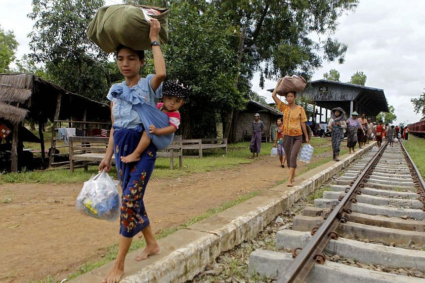Flood victims of KanGyi village receive aid from locals at the KanGyi railway station in Kanbalu, Sagaing Division, Myanmar on July 21, 2015.