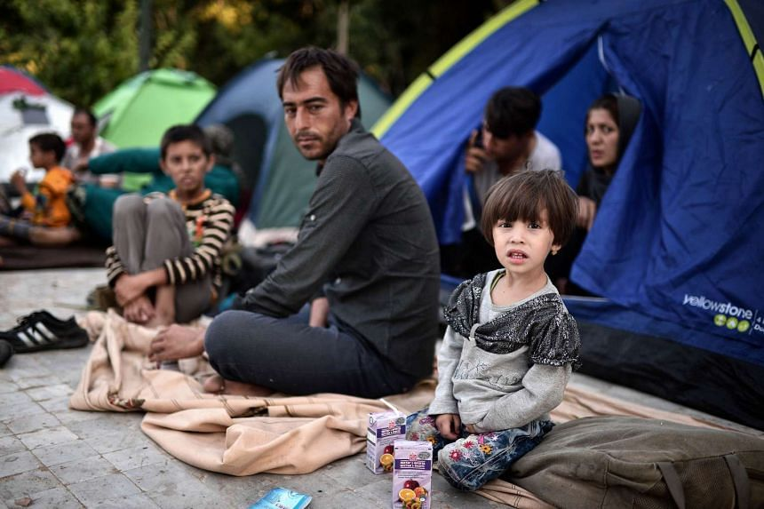 An Afghan family sits in a park in central Athens on July 25, 2015.