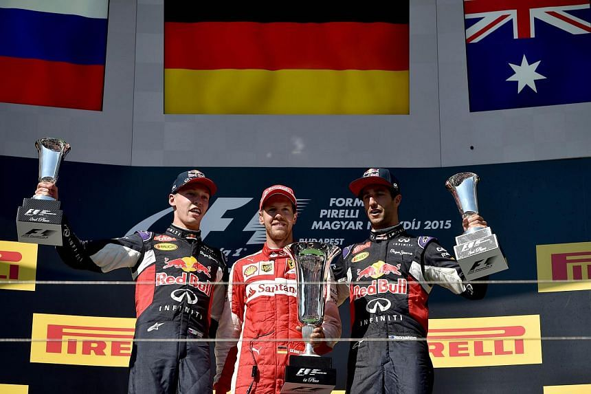 Second placed Infiniti Red Bull Racing's Russian driver Daniil Kvyat, winner Ferrari's German driver Sebastian Vettel and third placed Infiniti Red Bull Racing's Australian driver Daniel Ricciardo celebrate with their trophies on the podium after the