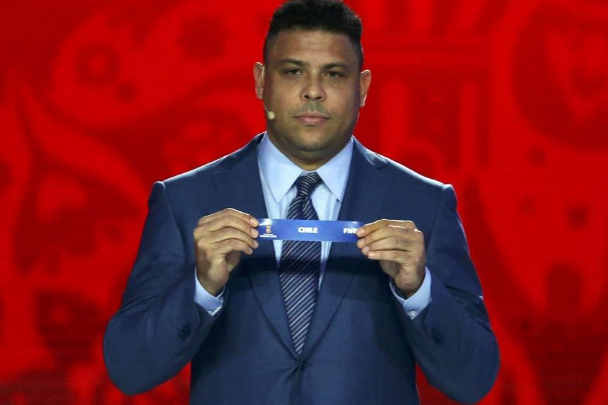 "Former soccer player Ronaldo of Brazil holds up the slip showing ""Chile"" during the preliminary draw."