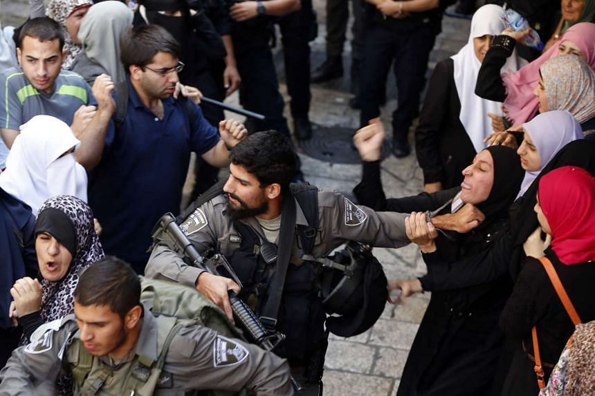 Members of the Israeli security forces scuffle with a Palestinian woman.