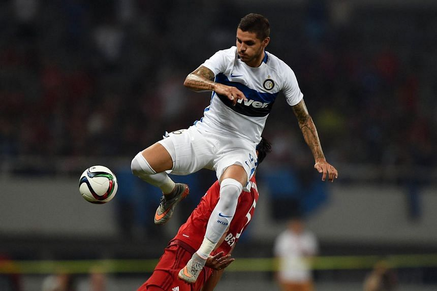 Inter Milan's Argentinian forward Mauro Icardi (top) and Bayern Munich's French defender Mehdi Benatia (partially hidden) vie for the ball during a friendly football match in Shanghai on July 21, 2015.