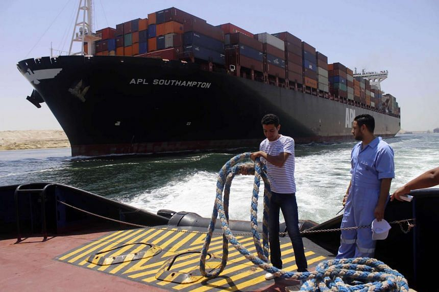 Employees at work on a container ship as they cross the new waterway of the Suez canal.