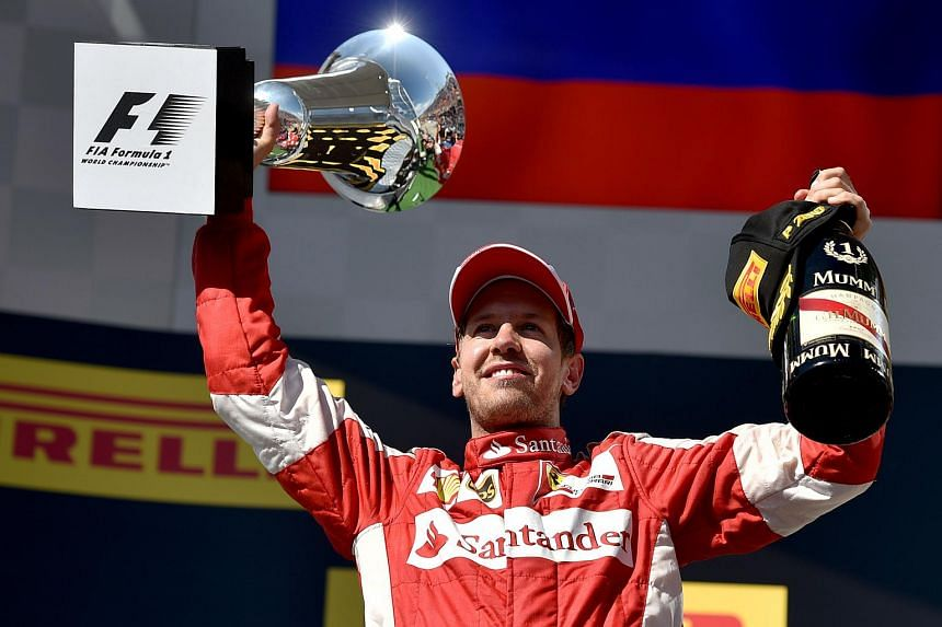 Ferrari's German driver Sebastian Vettel celebrates with his trophy on the podium after winning the Hungarian Formula One Grand Prix at the Hungaroring circuit near Budapest on July 26, 2015.