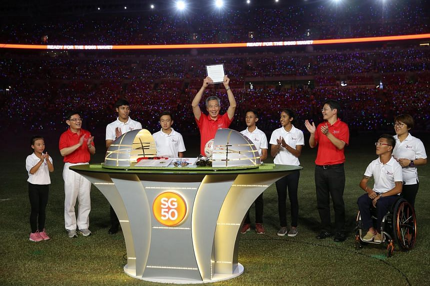 Prime Minister Lee Hsien Loong placing an item into the time capsule during the official opening of the Sports Hub during the MOE and MCCY-led Youth Day event called Youth Celebrate!, on Sunday, July 26, 2015.