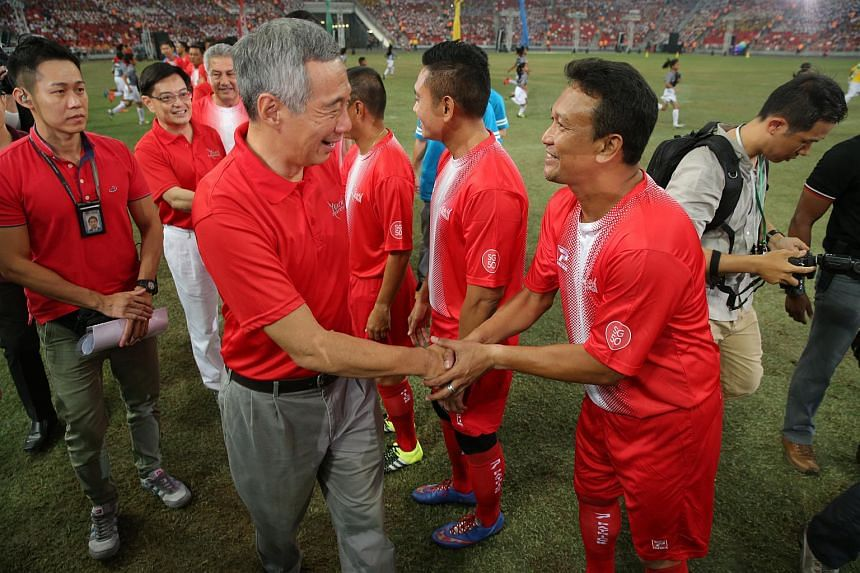 Prime Minister Lee Hsien Loong shakes hands with Fandi Ahmad who was taking part in Goal for a Cause, a modified football match where 50 budding student-athletes and 11 Singapore football veterans come together to raise funds for charity.