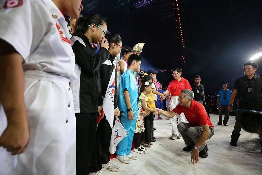 Prime Minister Lee Hsien Loong shaking hands with a student performer before taking his leave during the official opening of the Sports Hub.