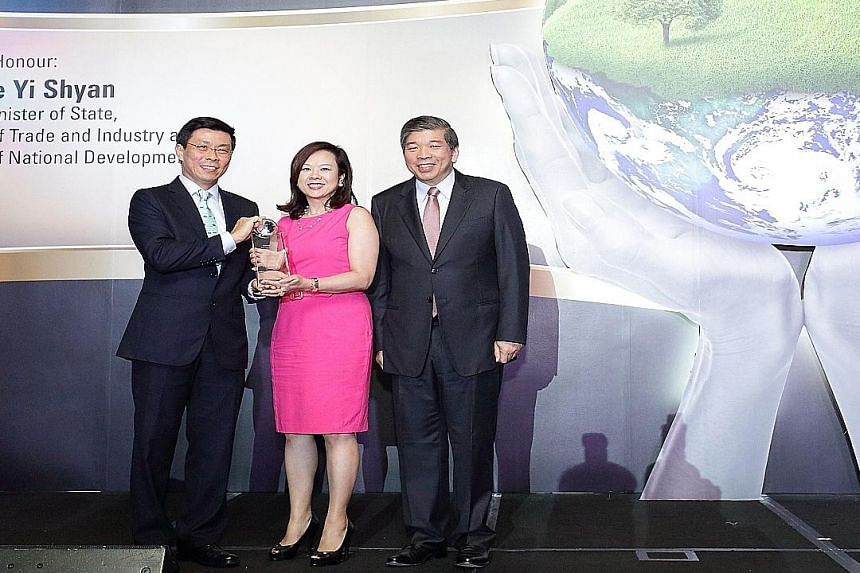 Ms Esther An receiving CDL's Sustainable Business Award 2014 in the category for large companies, flanked by Mr Lee Yi Shyan (left), Senior Minister of State for Trade and Industry and National Development, and Mr Teo Siong Seng, Singapore Business F