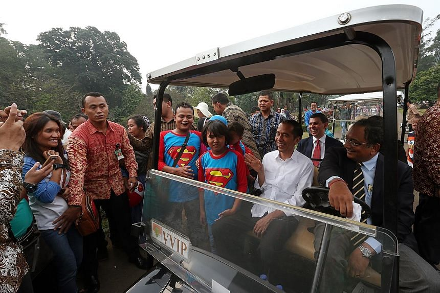 Members of the public swarming around President Joko Widodo's buggy during a ride around the Bogor Palace compound with The Straits Times team yesterday. Mr Joko uses Bogor Palace as his principal office, rather than the Merdeka Palace in Jakarta.