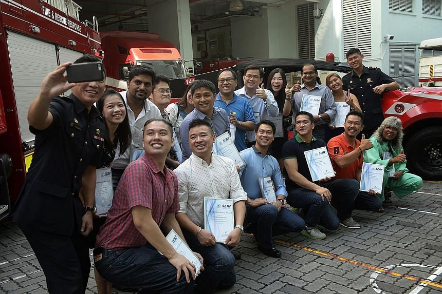 Lieutenant- Colonel Eric Chua, head of operations at the 1st SCDF Division, taking a wefie with the 16 men and women who received awards for their public spiritedness yesterday, as well as 1st SCDF Division commander Alan Chow (right). The award recip