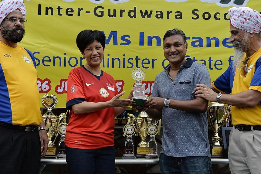 Senior Minister of State for Law and Education Indranee Rajah presenting coach V. Sundramoorthy with a lifetime achievement award from the local Sikh community for his contributions to Singapore football. With them are Gurdip Singh Usma (left), vice-