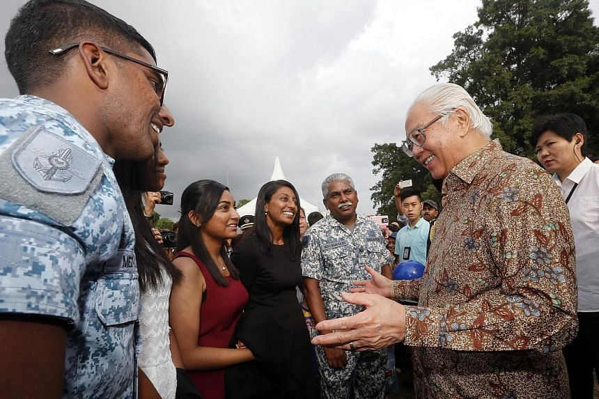 Military Expert (ME) 3 Brian Rajoo (centre) getting advice from President Tony Tan Keng Yam yesterday at an Istana exhibition to celebrate the 50th anniversary of the Singapore Armed Forces (SAF). The 52-year-old ME3 Rajoo was at the event with (from