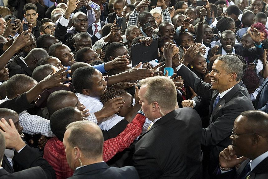 Mr Barack Obama (right) greeting the crowd after delivering his address to Kenyans at the Safaricom Indoor Arena in Nairobi yesterday. Much of his speech stressed his affinity with young Kenyans, a vital group in a country where 60 per cent of the po