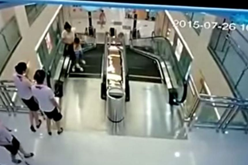 They reach the top of the escalator as nearby shop assistants look on.