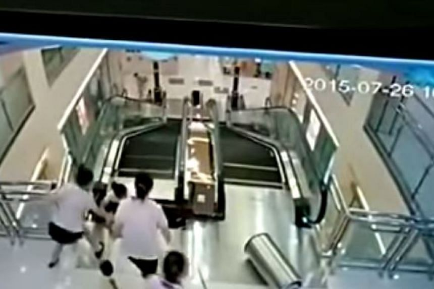 A shop assistant briefly grabs her hand in an attempt to pull her up.