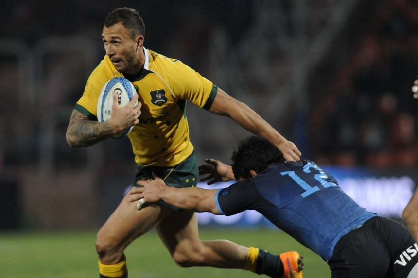 Australia's Wallabies' Quade Cooper (left) is tackled by Argentina's Los Pumas' Juan Pablo Socino (right) during the Rugby Championship 2015 test match at Malvinas Argentinas stadium in Mendoza, Argentina, on July 25, 2015.