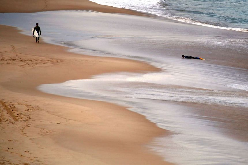 A boy lies on the shoreline as a surfer carrying his board walks along a beach in Australia May 25, 2015.