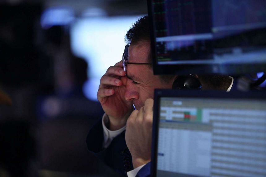 Traders work on the floor of the New York Stock Exchange (NYSE) on July 27, 2015 in New York City. The Dow Jones industrial average was down 150 points in morning trading following a steep overnight decline in the volatile Chinese exchange.PHOTO: AFP