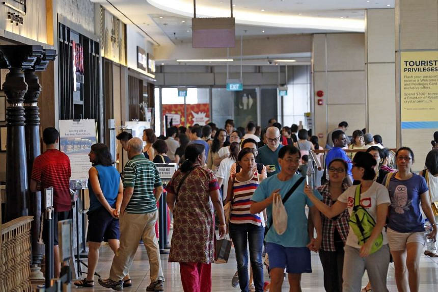 Shoppers walking along F&B outlets in the basement of Suntec City Mall near the Fountain of Wealth.