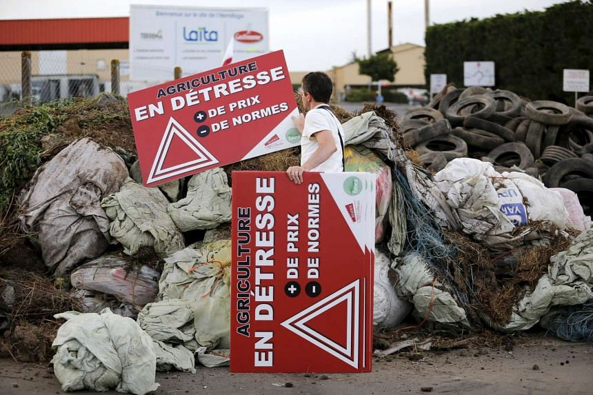French farmers block the entrance of a dairy in Ancenis, France, during a protest against a squeeze in margins by retailers and food processors.