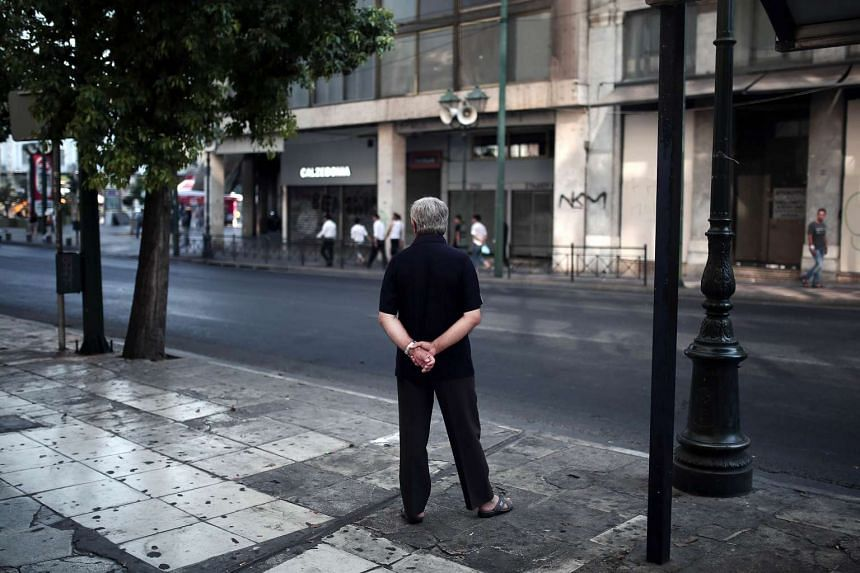 "A man waits at a bus stop in the center of Athens on July 26, 2015. Negotiators from the International Monetary Fund, European Union and European Central Bank -- together known as the ""troika"" -- were in Athens for talks on the third bailout. PHOTO:"