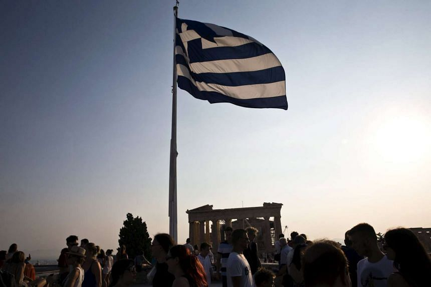 A Greek flag fluttering above tourists at Acropolis, an archaeological site in Athens.