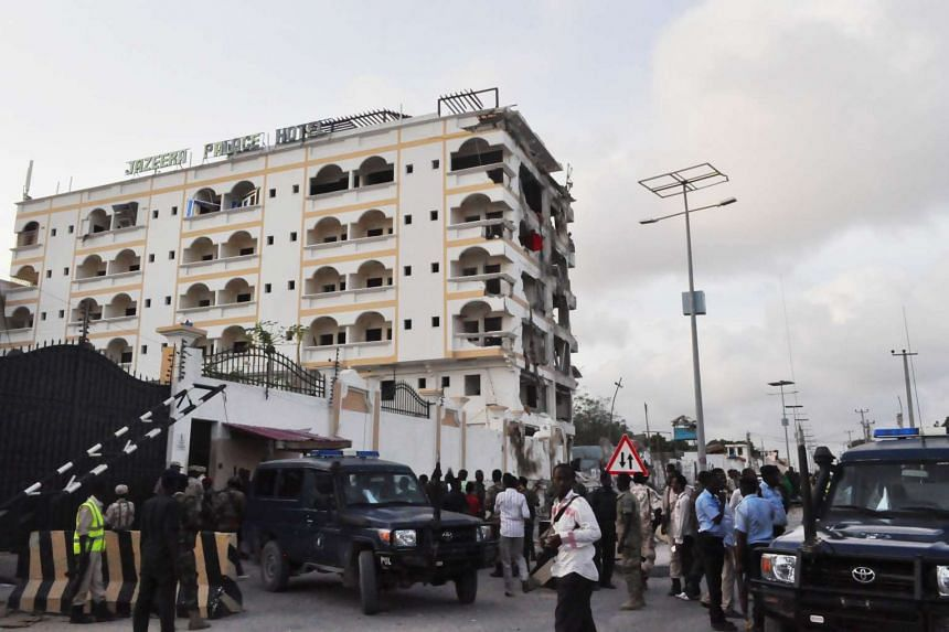 People stand in front of the damaged Jazeera Palace hotel.