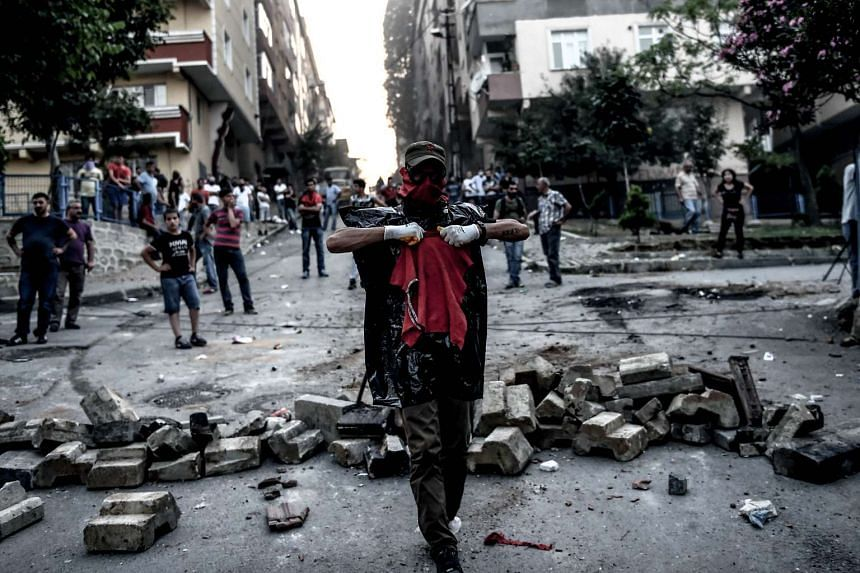 Left-wing protesters gather near a barricade during clashes with Turkish riot police in the district of Gazi.