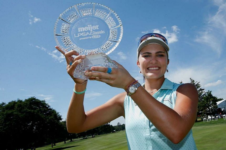 Lexi Thompson poses with the championship trophy.