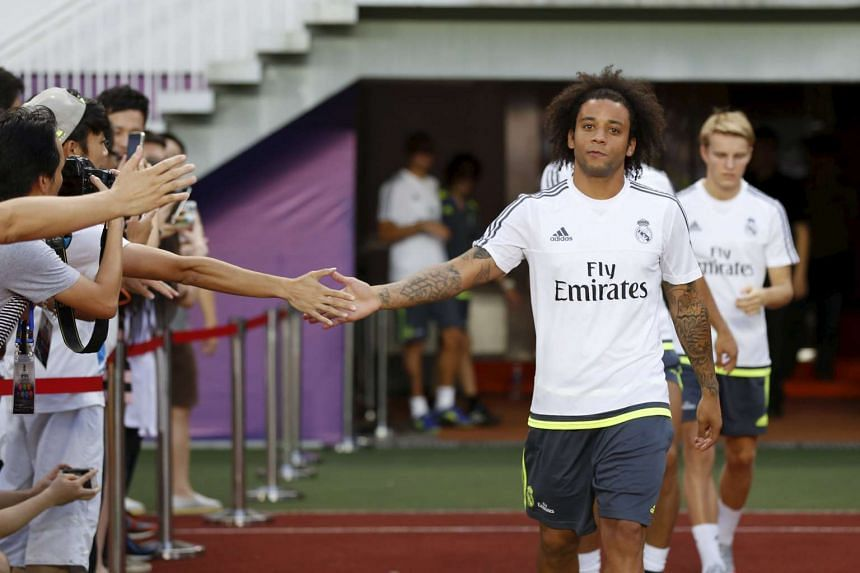 Real Madrid's Marcelo Vieira (right) shakes hand with journalist as he attends a training session at Tianhe Stadium, China on July 26, 2015.