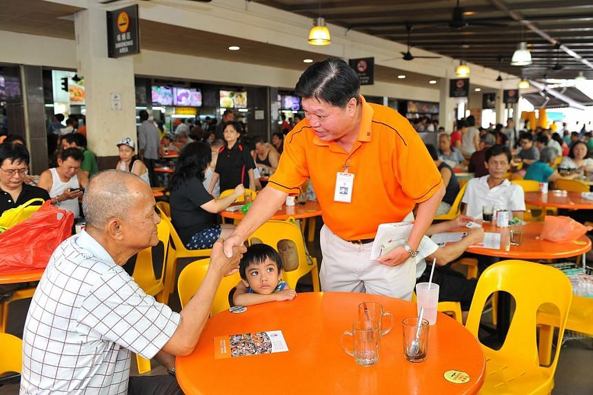 Mr Sebastian Teo, (center, standing) 68, President of National Solidarity Party, interacting with a resident during a walkabout around Tampines Street 81 on July 26 2015.