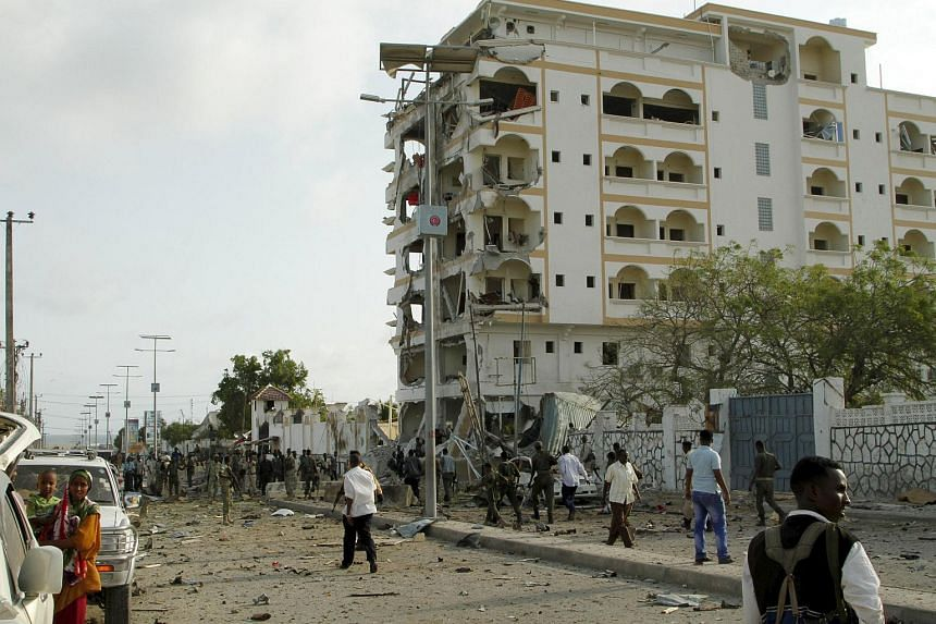 Somali government soldiers stand near the ruins of the Jazeera hotel after an attack in Somalia's capital Mogadishu, July 26, 2015. At least four people were killed on Sunday when Somalia's al Shabaab Islamist militant group drove a car packed with e