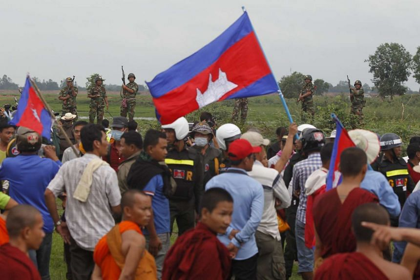 Cambodian soldiers stand guard as supporters of the Cambodian National Rescue Party (CNRP) arrive at a Cambodia-Vietnam border during a visit led by the party in Svay Rieng province on July 19, 2015.