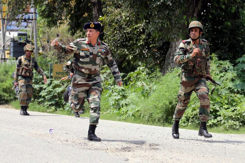 Indian Army soldiers run to take position as an exchange of fire continued with militants holed up in the police station at Dinanagar in Gurdaspur, India, on July 27, 2015.
