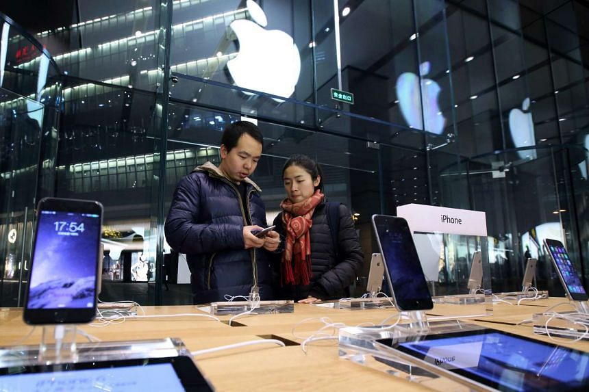 A couple look at an Apple iPhone 6 at an Apple store in the China Central Mall in Beijing, China, on Nov 11, 2014.