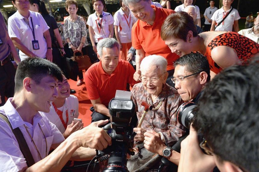 PM Lee Hsien Loong with pioneer Madam Lim Beck, 108, who is on the wheelchair, looking at a photograph.
