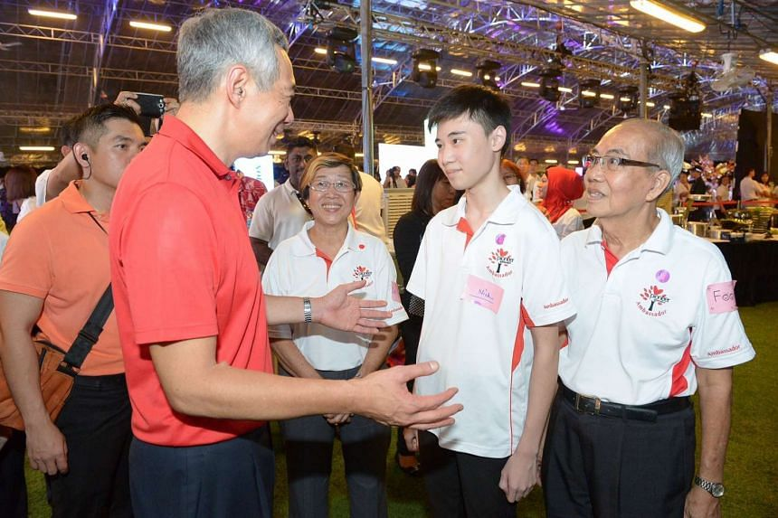 PM Lee Hsien Loong chatting with pioneer generation ambassadors (from left) Lai Siew Lian, 63, Nick Low, 18 and Foong Foo Kheong, 78.