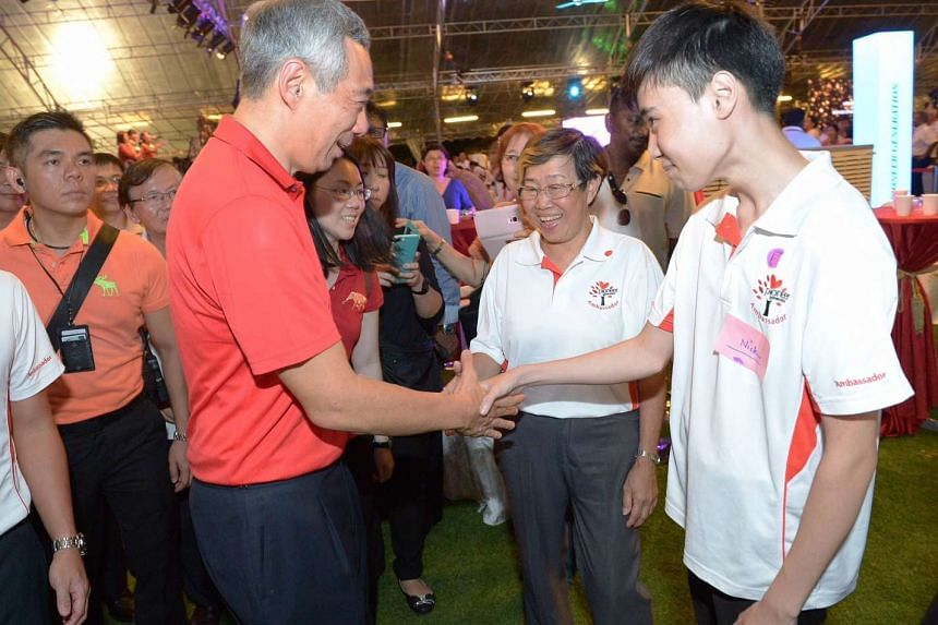 PM Lee Hsien Loong shaking hands with pioneer generation ambassadors:  Lai Siew Lian, 63, and Nick Low, 18.